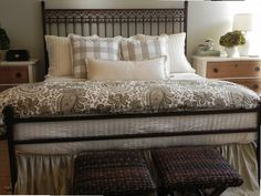 Bedroom by Holly Mathis Interiors - bed with iron headboard, grey and white paisley duvet cover, white quilt and buffalo check throw pillows - keywords: gray floral bedding gingham sham