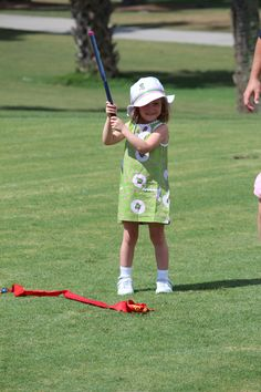 Learning a good swing, and looking like a master. The Littlest Golfer shift dress with 'resort print'