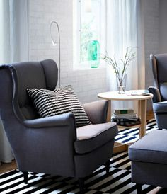 Grey wing chair with birch veneer side table and black/off-white rug