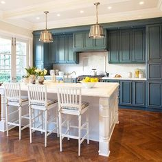 Love that the coastal feeling here is achieved with the blue-based cabinetry and white kitchen island. And I LOVE the herringbone floor!  { image via BHG } | www.cdgdesign.com