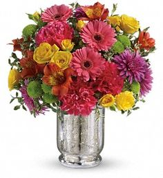Yellow roses, pink gerberas, orange alstroemeria, hot pink carnations, green button chrysanthemums and purple cushion spray chrysanthemums are accented with oregonia.