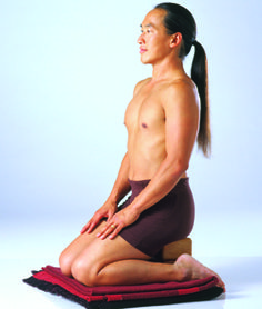 Rodney Yee in supported hero pose using props, for meditation