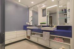A reforma deste banheiro reflete o dia-a-dia corrido do casal contemporâneo. A arquiteta Carine Cignachi projetou um espaço para cada um na bancada em duas cubas e nichos individualizados. O ambiente é contrastante e dinâmico, com hall de acesso de vidro, tornando todo este espaço moderno e funcional.