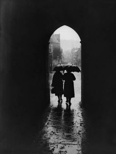 [CasaGiardino] two women, holding raised umbrellas, are silhouetted at the end of an arched passage-way on a rainy day, uk, photo by fox photos/hulton archive/getty images. Cozy Rainy Day, Rainy Night, Rainy Days, Night Rain, Night Light, Rainy Day Photography, Street Photography, Urban Photography, Vintage Photography