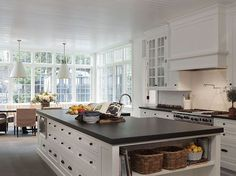 White cabinets with bronze hardware and dark countertops