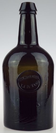 """Antique Bottles 335 - November - Alton Hampshire - This dark olive green bottle which dates to between c1830-1850 stands 9.4"""" tall. It has been blown in a three piece mould and has a pontil mark to the base. It bears an applied seal which is inscribed W. CROOK / LINTON. William Crook was the proprietor of the Crown Hotel in Lynton (Linton) North Devon between the 1840's and 1860's."""