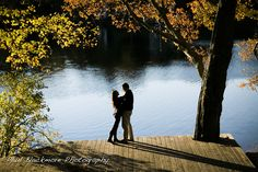 Fall engagement shoot revealing the foliage against the pond with a silhouette of of two lovers surrounded by beauty.
