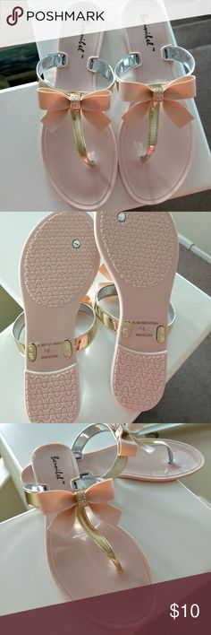 Bonnibell Jelly Flip Flops with Bows Light pink Bonnibell jelly flip flops with light pink jelly bows and gold T-straps. Bows have rhinestones in center. New. Never worn. Size 7 1/2. Photo with model is only to show what they look like on. I have seen the exact same sandals in several other brands such as Soda, Polyvore, Truffle, Sunshine. Valentino has some that are very similar. Bonnibell Shoes Sandals