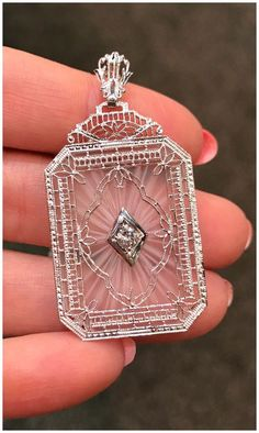 A beautiful Art Deco era rock crystal pendant with filigree and diamond details. From Under the Crown jewelry.