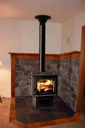 Wood Stove Hearth Rendition Like the wood trim around the stone (basement living rooms wood stove) Wood Burning Stove Corner, Wood Stove Wall, Wood Stove Surround, Wood Stove Hearth, Fireplace Hearth, Stove Fireplace, Wood Burner, Fireplace Surrounds, Fireplaces