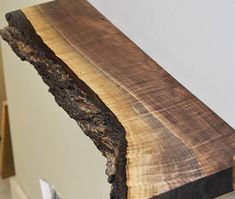 Featured is a live edge floating shelf made of high end, solid walnut wood harvested from forests in Northeast Ohio. This product is handmade in our workshop by Wood Bark, Wood Slab, Raw Wood, Walnut Wood, Dark Wood Shelves, Live Edge Shelves, Walnut Shelves, Floating Shelf Under Tv, Rustic Floating Shelves