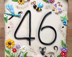 This beautifully hand made ceramic house sign is personalised with your own house number. Decorated with a dragonfly pretty tulip flowers and a cute cat amongst the foliage. House Name Plaques, House Number Plaque, Pottery Houses, Ceramic Houses, House Address Numbers, Ceramic House Numbers, Dragonfly Art, Rock Crafts, Polymer Clay Crafts