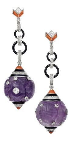 A pair of Art Deco platinum, carved amethyst, diamond, coral and enamel earrings, French, circa 1930. A pair of ancient carved amethyst boules set with a scattering of twelve old cut diamonds, each suspended from classic Art Deco diamond, coral and black enamel sections and terminals all set in platinum. Length 5.7cms. #ArtDeco #earrings