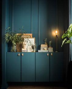To IVAR-skap er malt i samme nyanse som veggene og fylt med bøker, kunst og planter. På toppen står det ei lampe.