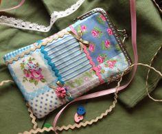 Funda para móvil en tejido imitación patchwork en tonos azules y rosas. Decorado ademas de picunela en varios colores y lazo de raso con una florecita realizada con picunela rosa. El interior es en color beige con flores azules Boquilla color plata 9 cm.  17 euros.