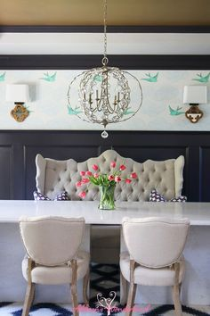 A stunning Anthropologie style vintage chic dining room! Daydream wallpaper, a metallic gold ceiling and dark gray paneling are the perfect backdrop for cream tufted chairs and banquette alongside teal wingback end chairs. All of these elements are offset by a navy ikat rug and a stunning gold / crystal globe chandelier!