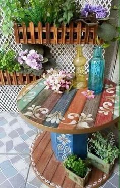 """Cool & pretty spool table [ """"Spool turned into a side table. I love the colors and the cute little stencil on this. :)"""", """"Great inspiration for creating a table from an industrial spool. This is a picture only."""", """"JOYCE: Wonder if we could make these out of the abandoned 2 spool tables next door??"""", """"I like those planters maybe even could be connected to our railings on patio ?"""", """"I LIKE THE LATTICE FOR THE RECYCLE BIN CONTAINER WITH THE HANGING PLANTERS"""", """"Cool design for table t..."""