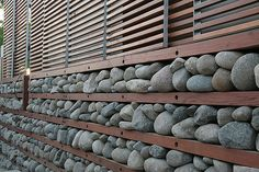 """Passive Cooling: Rock Wall. A Natural Thermostat:    """"Large rocks squeezed into together by 'wood shelves' insulate the South face of the house. The rocks absorb the heat during the day lowering the solar gain. At night the rocks give heat back into into the air as the temperature outside drops. The rock wall and the desert climate work in concert to passively cool the house."""""""