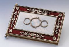 A notebook in red and white guilloche enamel by Faberge, with diamonds and moonstones. This was given to Queen Victoria by Tsar Nicholas II and Alexandra when they visited Balmoral in 1896, with their signatures on the first page. Later, Queen Victoria collected the signatures of those visiting her during her Diamond Jubilee in 1897.