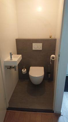 Resultaat na toilet renovatie. Tegels betonlook, mat wit op de muur. Strak wit fonteintje en strakke pot. Moderne wc.