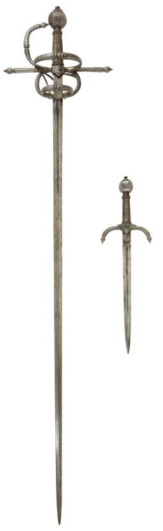 """[#Claudio] SWEPT HILT RAPIER AND COMPANION LEFT HAND DAGGER Early 20th century, by Anton Konrad and built on matching 16th century blades. Iron hits beautifully chased in high relief scrolling foliage, flowers and fruit. Fine wire wrapped grips with turban form terminals. The blades, 41"""" and 12 ½"""" respectively, each with maker's marks to each side of the ricasso and with deep fuller marked * PAR * CE * SIGNE * TU * VAINCRAS * (BY THIS SIGN YOU OVERCOME) each side."""