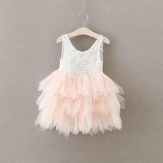 This dress is just beautiful! It includes a delicate white lace bodice with tiered tutu skirt. It also has an embellished lace and pearl detail on the bodice. T