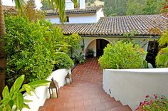 Saltillo tiles and a curved staircase flanked with lanterns lead down to the estate.