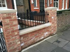 Pretty West London red brick front wall with stone effect caps and iron railings