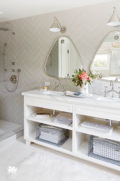 A bathroom vanity featuring dual sinks, Brittanicca™ from Cambria's Marble Collection™, and perfectly aligned symmetry enhance the beautiful simplicity of this white bathroom.