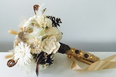 A rustic and woodsy blend of sola flowers, pine cones, pheasant feathers, dried grass plumes and ghost leaves with a wrap of burlap and French braid gold ribbon