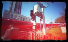 chris-keeney-pinhole-photography-matchbox-sd  Color 35mm film pinhole photograph of the San Diego trolley passing by man waiting at intersection. Created with DIY matchbox pinhole camera
