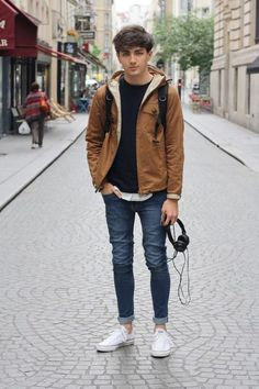blue rolled up jeans, a black sweater, an ocher jacket