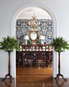 Gorgeous dining room - Blue and white Lhasa wallpaper from Brunschwig & Fils, French chandelier, symmetrical tablescape on the sideboard, Boston ferns - Photo by Michael Graydon, Design by Michael Angus - Canadian House & Home