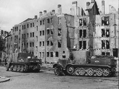 Several SdKfz 8 heavy halftracks passing through a damaged city devoid of people