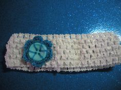 White stretchy headband with a handmade crocheted blue flower button. 5 inch headband can stretch to 11 inches. Flower measures 1.5 inches