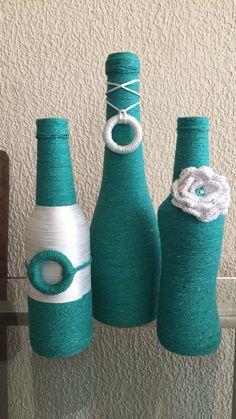 Trio de garrafas decoradas com barbante e flor de crochê.