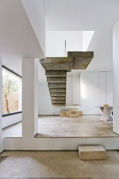 CASA C-51 BY ÁBATON ARQUITECTURA. An award winning sustainably built house in Spain with a raw concrete central staircase. The suspended stairs link the entry and living room with the second floor.