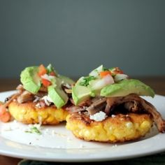 Mexican corn cakes topped with caramelized shredded pork, avocado, and pico de gallo