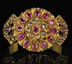 A DIAMOND AND RUBY SET GOLD BRACELET, MOROCCO, 19TH CENTURY featuring a raised central roundel set with a row of faceted pink rubies around a higher set roundel mounted with diamonds in a flowerhead motif, hinged compartment to reverse with green and red enamel, the armband featuring petal shaped terminals set with diamonds and a central ruby, both sides hinged, one to reveal opening