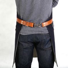 """Mens Apron - Indigo Selvage Denim   Hardmill- 14 oz. black selvage denim - 11.5 oz. cotton duck backing - 7 oz. hand-dyed leather - Copper rivets Features: - Utility ring for hand towel - Snap hook for easy fastening - Adjustable to fit 30"""" - 40"""" waists - Apron measurements: 30"""" wide x 34"""" tall $220"""