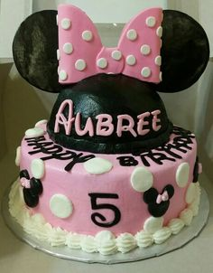 """Minnie mouse cake. I used two 8"""" round cake pans and half of the Wilton ball cake pan. The cakes are iced in buttercream and the number & letters, are fondant cutouts. The ears are 4"""" circle cardboard covered in fondant and attached with a skewer. The bow is made of gumpaste and fondant mixture i used the minnie mouse bow cut out from https://www.jbcookiecutters.com/"""