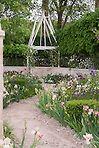 Irises, Paeonia peonies, pastel soft colors in pink theme, path walkway, wall, gazebo, spring flowers, gravel dirt path, pretty May or June backyard garden scene view