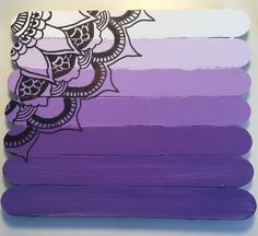 7 popsicle sticks lined up Painted in a purple ombré A mandala drawn on top
