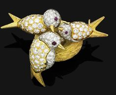 A diamond and ruby brooch, by Tiffany & Co., 1960s  Modelled as three birds perched around a nest, the bi-coloured feathers pavé-set with brilliant-cut diamonds, to the textured gold tails and ruby-set eye detail, the nest of textured gold, centring three pearl eggs, signed Tiffany & Co., mounted in 18 carat white and yellow gold, diamonds approximately 2.00 carats total, gross weight 26.7 grams, width 4.8cm