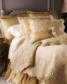 rich looking gold and cream bedding; matelasse bedspread and layered pillows