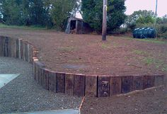 curved retaining wall from railway sleepers on end Stone Retaining Wall, Sleeper Retaining Wall, Retaining Walls, Garden Retaining Wall, Back Gardens, Outdoor Gardens, Traverses, Sleeper Wall, Patios