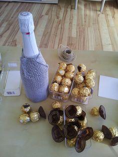 Flasche mit etwas ummanteln damit die Rocher kleben bleiben und bei alle Rocher das braune Papier abschneiden ( nicht abziehen, da sonst die goldene Folie aufgeht)