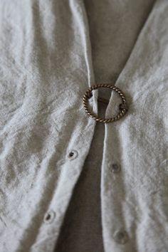 Brooch through eyelets as fastener.