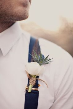Sweet boutonniere with paper white and thistle, wrapped in twine. Love the sapphire blue suspenders. #wedding #groom #groomsmen
