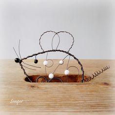 Bílá myška :) Drátovaná myška z černého žíhaného drátu zdobená černými a bílými skleněnými korálky. Myšku můžete zavěsit jen tak na hřebíček na zeď, opřít na oblíbené komodě nebo zavěsit na řetízku s háčkem, který bude s myškou dodán ( viz. foto, řetízek lze odepnout ). Rozměry : šířka s fousky a ocáskem cca 17 cm, výška 11 cm, délka po ...